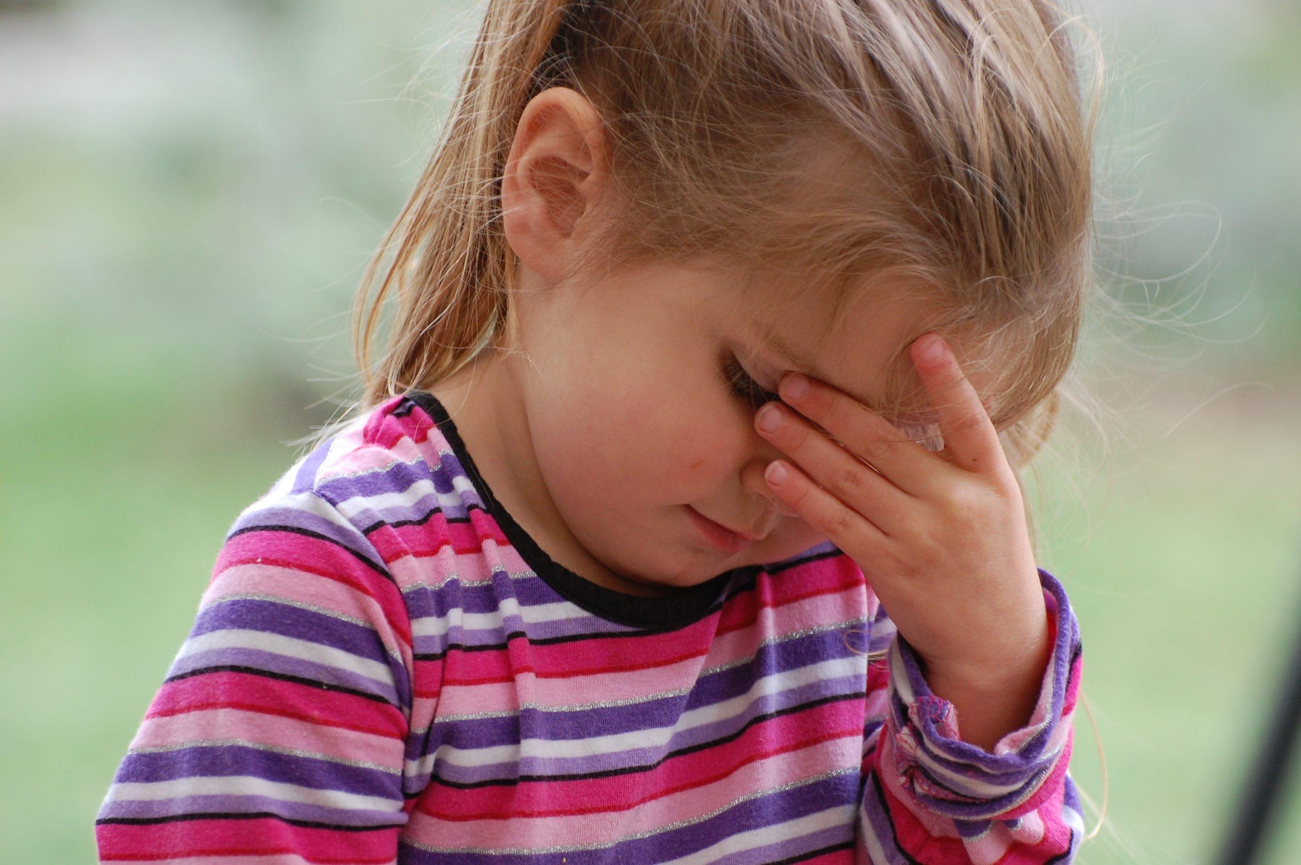 enfant se tenant la tete car il a mal à la tete
