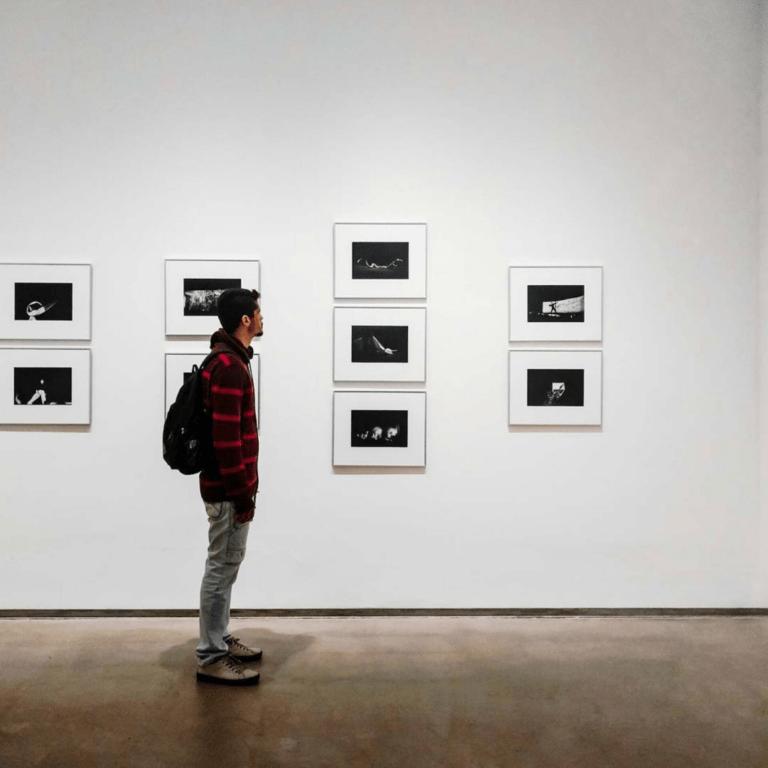 Photo d'une personne debout devant un mur blanc avec des cadres photos