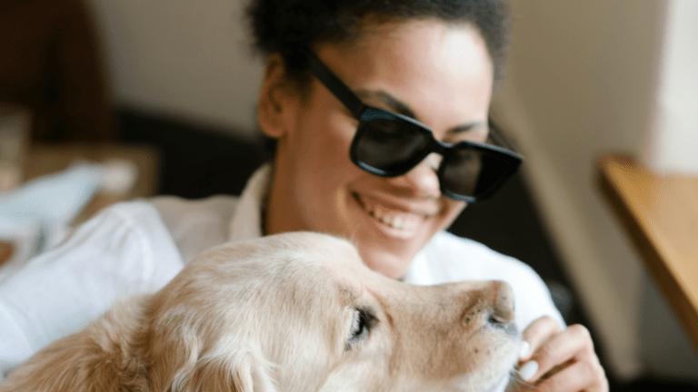 photo d'une femme avec des lunette de soleil, donnant a manger a son chien