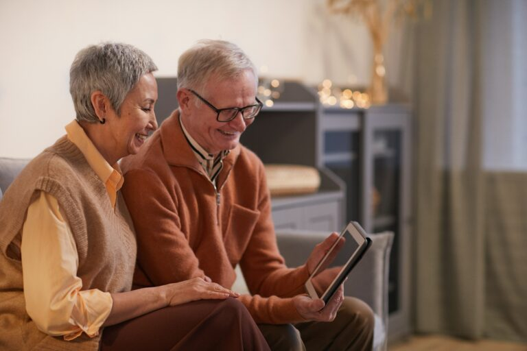 photo de deux personnes de plus de 50 ans regardant une tablette