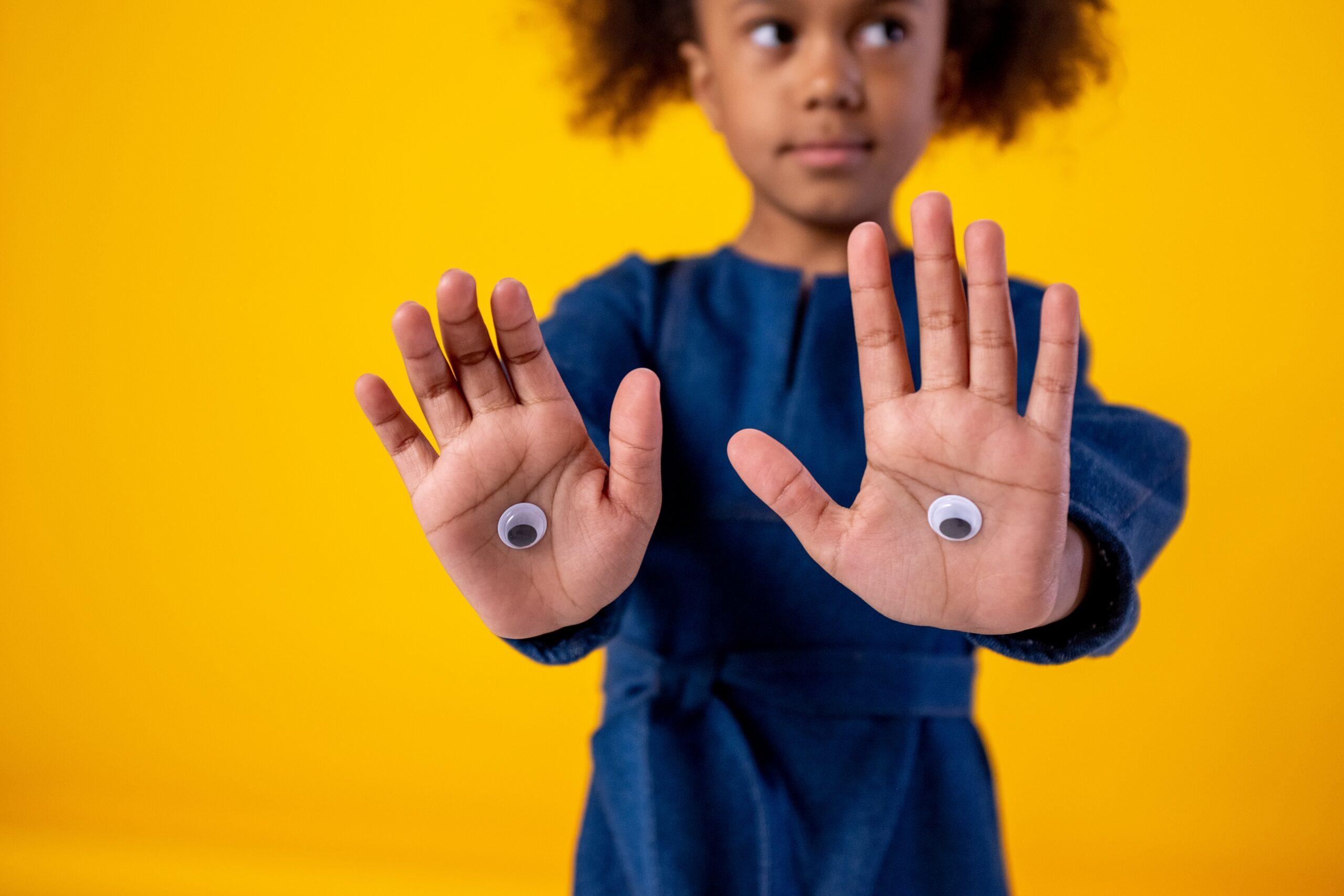 Photo d'une petite fille avec des autocollant d'oeil collés sur ses mains